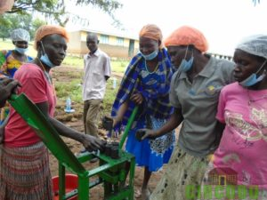 Participants learning how to use hands to stick briquettes
