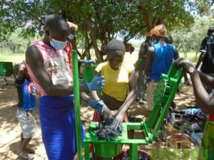 Participants engaging in production of the Honey Comb briquette