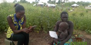 An enumerator conducting a survey with one of the respondents.